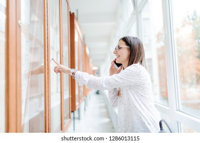 Smiling collage girl with brown hair and eyeglasses using smart phone for calling her colleague to report who passed exams, pointing with finger at noticeboard. University building interior.