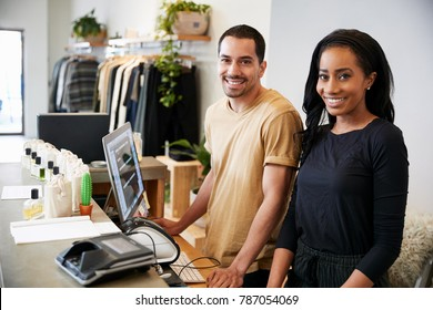 Smiling colleagues behind the counter in clothing store