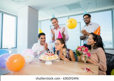 Smiling colleagues celebrating birthday of woman in office