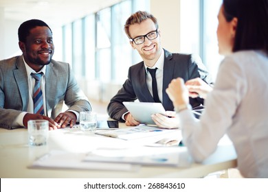 Smiling colleagues discussing working ideas in office