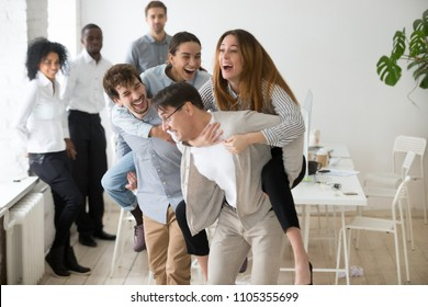 Smiling colleagues having fun, laughing and doing piggyback ride at workplace, coworkers playing games during work break or teambuilding meeting in office, workers enjoy spending time together