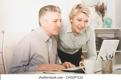 Smiling colleagues look interesting information on internet on laptop at desk at ofice