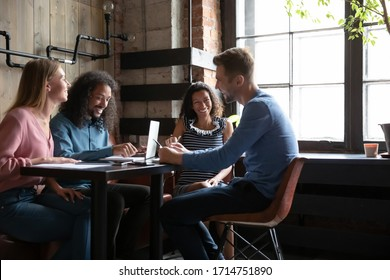 Smiling colleagues sit gather in cafe work together on laptop discussing ideas or project, happy diverse friends or students have fun laugh and talk studying in coffeehouse