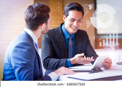 Smiling colleagues using tablet with financial analysis graphs. Closeup of two adult businessmen sitting at table and using tablet computer