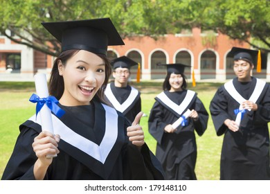 smiling college graduate holds a diploma and thumb up