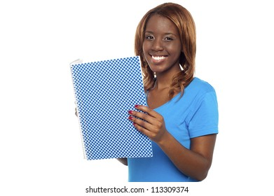Smiling college student holding notebook and looking at camera