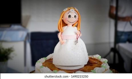 smiling communion doll on cake. communion simbol. comunnion celebration. first holy communion