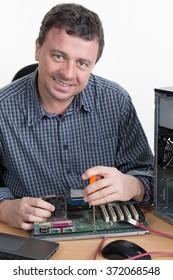 Smiling computer engineer repairing hardware  in bright office