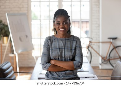 Smiling confident african american female corporate leader executive standing arms crossed in modern office space looking at camera, happy entrepreneur professional business woman manager portrait