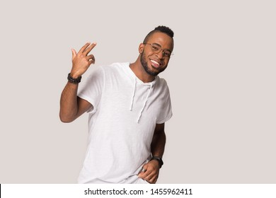Smiling confident African American man in glasses moving, having fun, making funny gesture, happy funny male in casual clothes looking at camera, posing dancing isolated on grey studio background