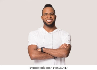 Smiling confident African American man in glasses standing with arms crossed, happy young mixed race male in white T-shirt casual clothes looking at camera, posing isolated on grey studio background