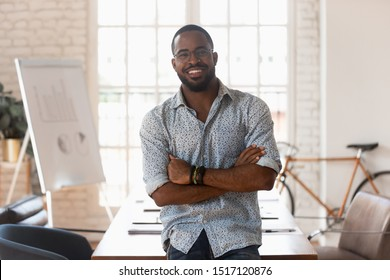 Smiling confident african american young businessman standing with folded hands, looking at camera. Portrait of happy handsome male manager satisfied with company career at modern creative office.