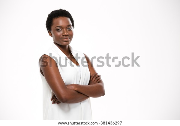 Smiling confident african american young woman standing with arms crossed over white background