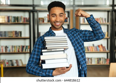 Smiling confident african male student holding stack of books and showing his muscles while standing in a library