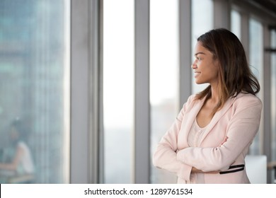 Smiling confident african millennial businesswoman looking at window think about future hope for new opportunities, thoughtful black female executive dream enjoy success, business vision concept