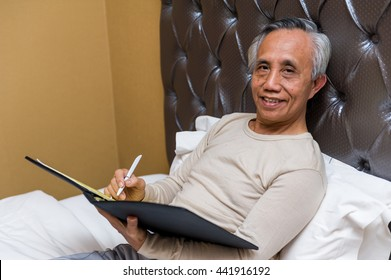 Smiling confident Asian senior male with file and pen in bed.