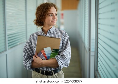 Smiling confident attractive young female color design specialist embracing sketchpad and color swatch and standing in corridor while looking aside