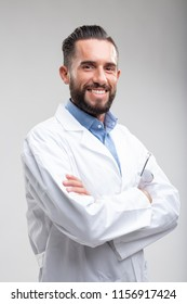 Smiling confident bearded male doctor in a white lab coat standing with folded arms, upper body over white