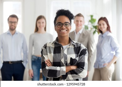 Smiling confident black company employee standing with diverse colleagues at background, happy african female manager intern worker looking at camera, business leader coach in office portrait