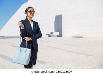 Smiling confident business lady on her way to office. Elegant young woman in formal suit and sunglasses with blue stylish bag walking outdoors through square. Fashion concept