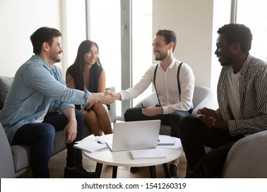 Smiling confident business partners shaking hand at group negotiations, making agreement or signing contract, colleagues greeting handshaking at meeting, diverse employees at briefing