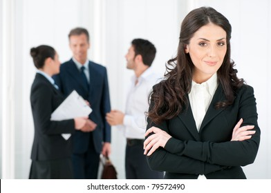 Smiling confident business woman looking at camera with her colleagues in background at office