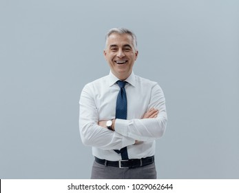 Smiling confident businessman posing with arms crossed and looking at camera