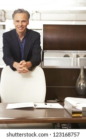 Smiling confident businessman standing behind his office chair leaning on it in a stylish modern office