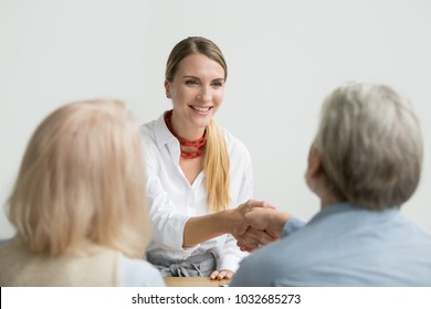 Smiling confident businesswoman applicant shaking hand of senior hr manager making good first impression at job interview, friendly lawyer or financial advisor handshaking older aged couple at meeting