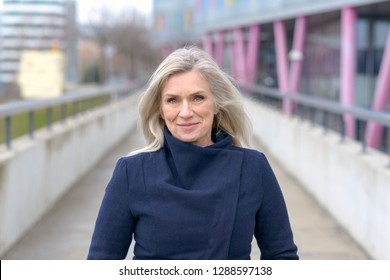 Smiling confident businesswoman walking through town along a pedestrian walkway approaching the camera with a smile of pleasure