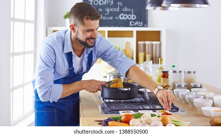 Smiling and confident chef standing in large kitchen