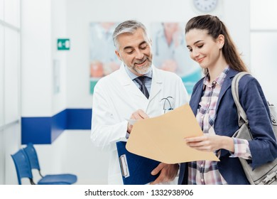Smiling confident doctor explaining medical records to a young female patient