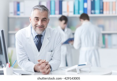 Smiling confident doctor at the reception desk, medical staff working on the background