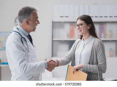 Smiling confident doctor shaking hands with a female patient in the office, she is holding medical records