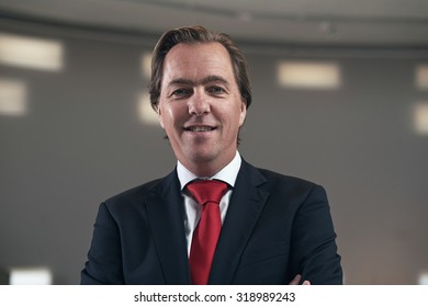 Smiling confident entrepreneur with red tie in empty room.