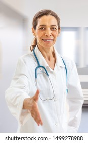 Smiling confident female doctor smiling and giving a handshake to the viewer, point of view shot,hospital corridor background