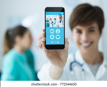 Smiling confident female doctor holding a touch screen smartphone and medical staff on the background, medical app concept