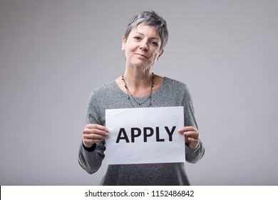 Smiling confident friendly woman holding a sign - Apply - in front of her chest over grey with copy space