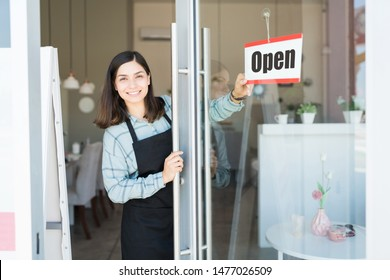 Smiling confident Latin owner turning open sign on glass door of spa