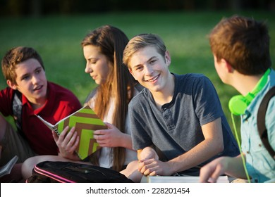 Smiling confident male teenager with friends outdoors