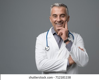 Smiling confident mature doctor posing on gray background, he is looking at camera