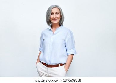 Smiling confident middle aged business woman standing isolated on white background. Old senior businesswoman, 60s grey haired lady professional female manager, leader looking at camera, copy space.