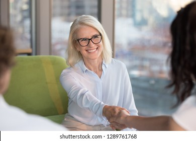 Smiling confident old mature woman job seeker applicant handshaking hr making good first impression at interview meeting, happy satisfied middle aged businesswoman shaking hand getting hired concept