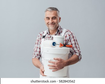 Smiling confident painter and decorator posing with a paint roller and buckets, he is looking at camera