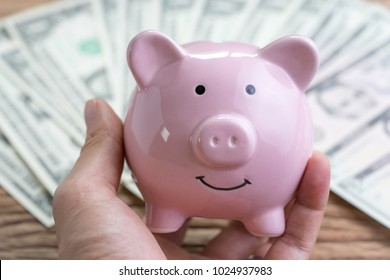 Smiling with confident pink piggy bank in hand with pile of US Dollar banknotes on wooden table in background using as financial savings money account or invest for future growth of interest compound.
