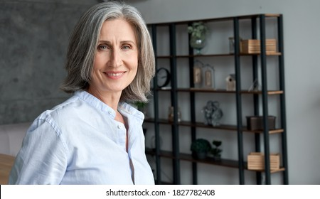 Smiling confident stylish mature middle aged woman standing at home office. Old senior businesswoman, 60s grey-haired elegant lady executive business leader manager looking at camera, portrait.