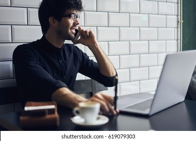Smiling confident successful creativity entrepreneur in eyewear having conversation with colleague planning working process for online business via modern mobile phone sitting in cafeteria indoors