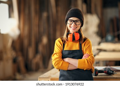 Smiling confident young female joiner in apron standing near workbench and looking at camera friendly while working in craft workshop