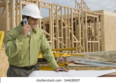 Smiling construction worker with cellphone and blueprints at site