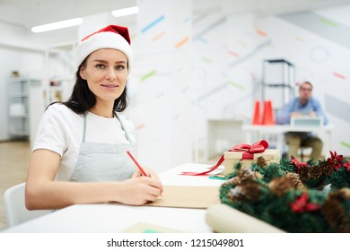 Smiling content attractive young lady in Santa hat sitting at table in modern office of company and looking at camera while drawing in sketchpad